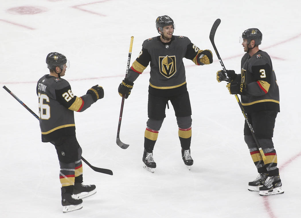 Golden Knights defenseman Brayden McNabb (3) celebrates his goal with Golden Knights center Paul Stastny (26) and Golden Knights defenseman Shea Theodore during the third period of an NHL hockey g ...