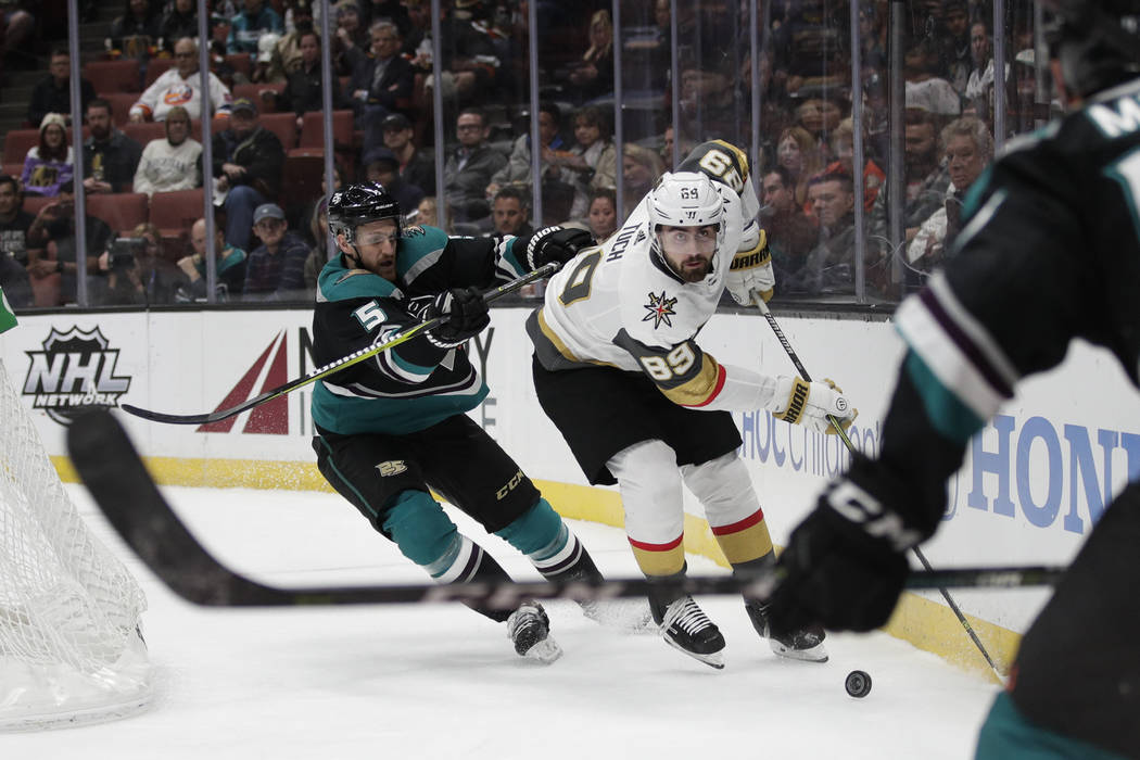 Vegas Golden Knights' Alex Tuch, right rear, moves the puck past Anaheim Ducks' Korbinian Holzer during the first period of an NHL hockey game Friday, March 1, 2019, in Anaheim, Calif. (AP Photo/J ...