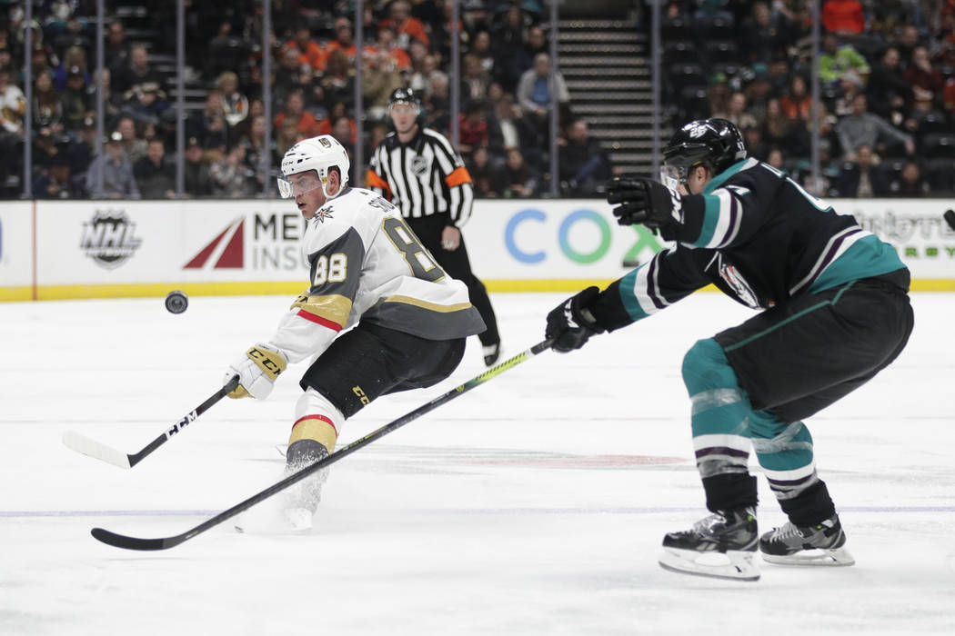 Vegas Golden Knights' Nate Schmidt, left, controls the puck under pressure from Anaheim Ducks' Hampus Lindholm during the third period of an NHL hockey game Friday, March 1, 2019, in Anaheim, Cali ...