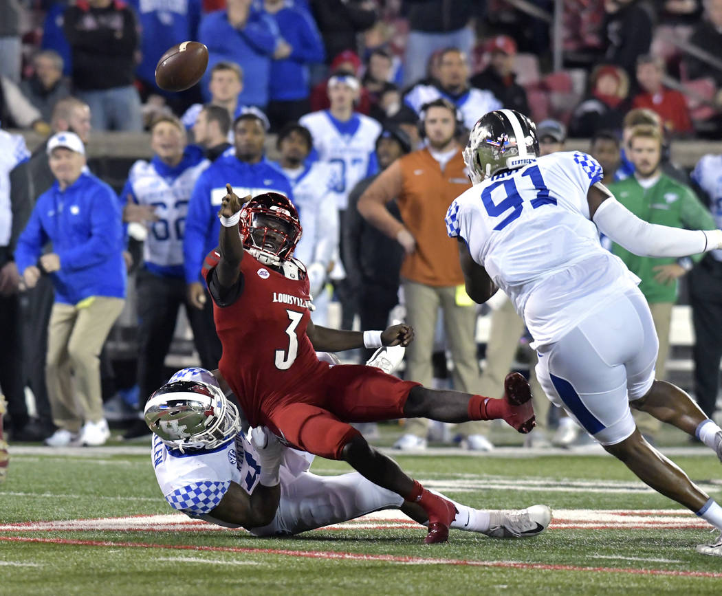 Louisville quarterback Malik Cunningham (3) attempts a pass while being brought down by Kentucky linebacker Josh Allen (41) during the first half of an NCAA college football game in Louisville, Ky ...