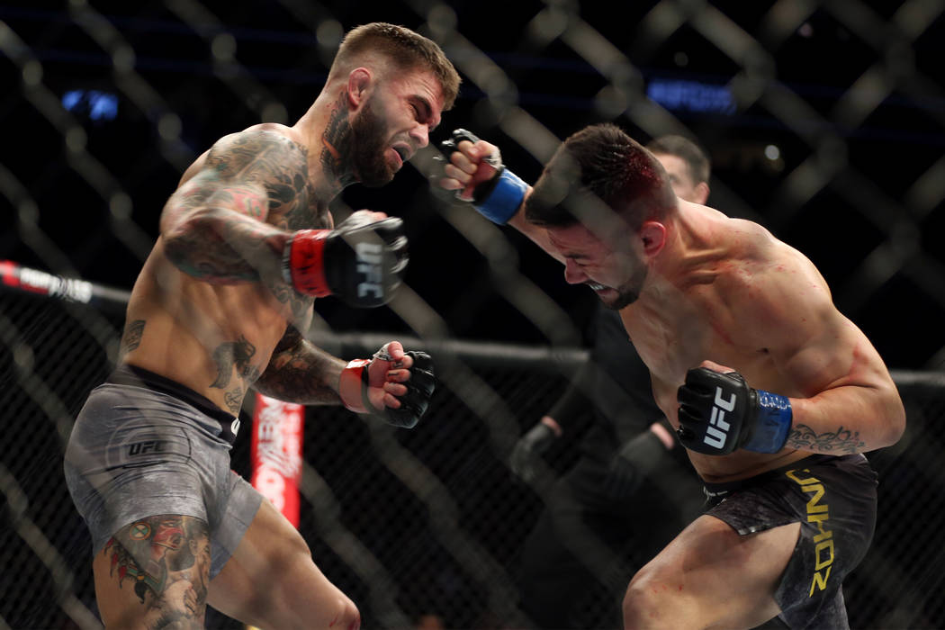 Pedro Munhoz, right, connects a punch to knockout Cody Garbrandt in the first round of the bantamweight bout during UFC 235 at T-Mobile Arena in Las Vegas, Saturday, March 2, 2019. (Erik Verduzco/ ...