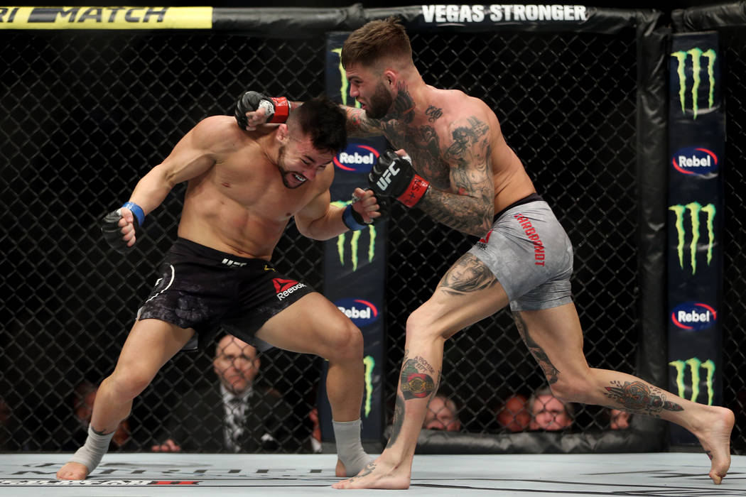 Pedro Munhoz, left, battles Cody Garbrandt in the first round of the bantamweight bout during UFC 235 at T-Mobile Arena in Las Vegas, Saturday, March 2, 2019. Munhoz won by way of knockout in the ...