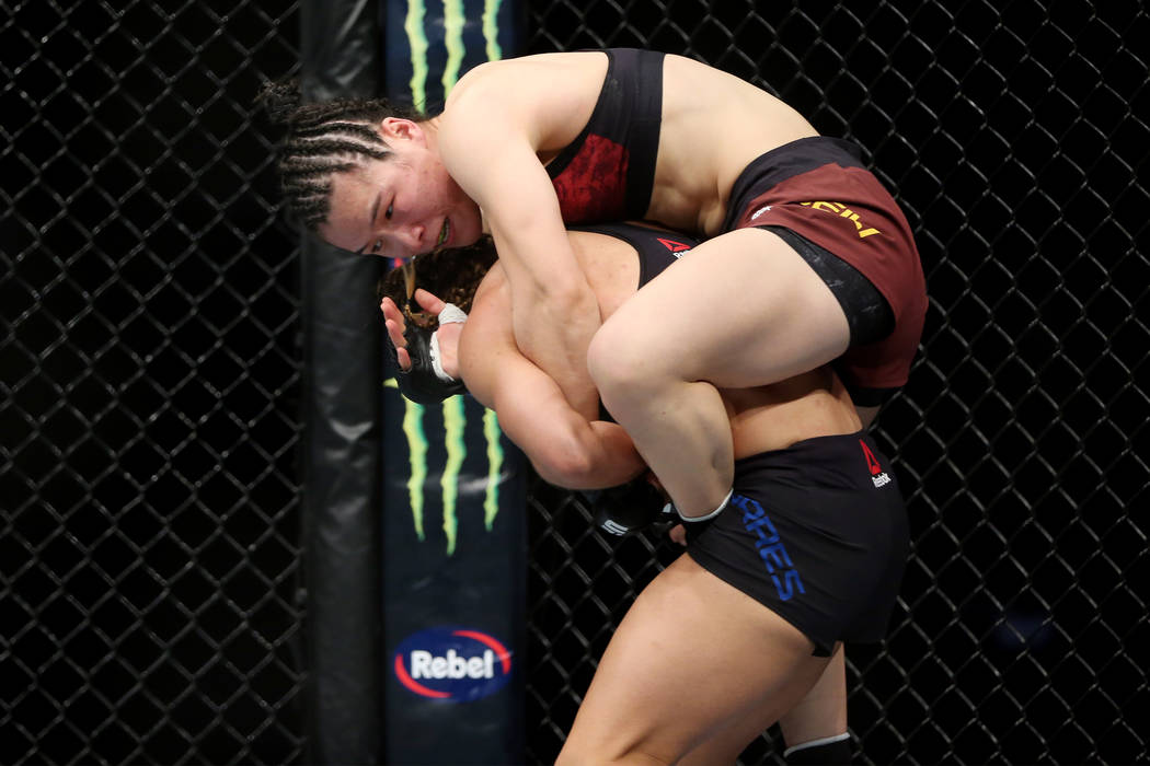 Weili Zhang, top, grabs to Tecia Torres in the womenÕs strawweight bout during UFC 235 at T-Mobile Arena in Las Vegas, Saturday, March 2, 2019. Zhang won by unanimous decision. (Erik Verduzco ...