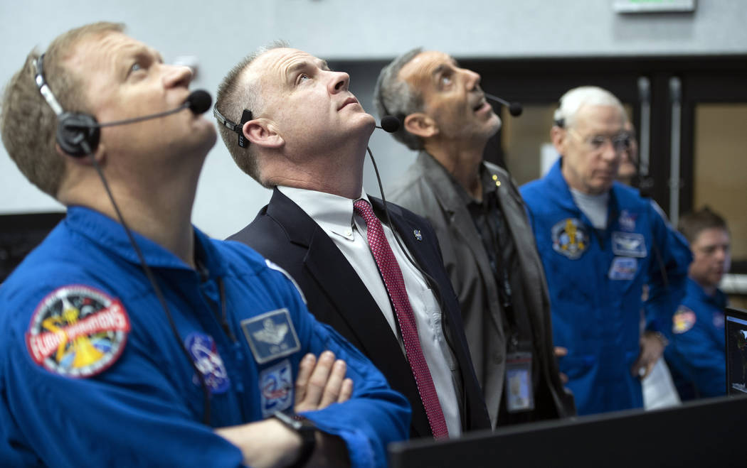 NASA astronaut Eric Boe, assistant to the chief of the astronaut office for commercial crew, left, and Norm Knight, deputy director of flight operations at NASA's Johnson Space Center watch the la ...