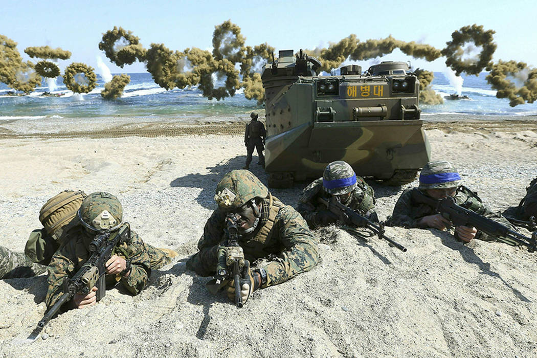 Marines of the U.S., left, and South Korea, wearing blue headbands on their helmets, take positions after landing on a beach during the joint military combined amphibious exercise, called Ssangyon ...