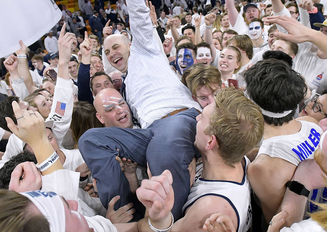 Utah State coach Craig Smith celebrates with fan on the court after Utah State defeated No. 12 Nevada 81-76 in an NCAA college basketball game Saturday, March 2, 2019, in Logan, Utah. (Eli Lucero/ ...