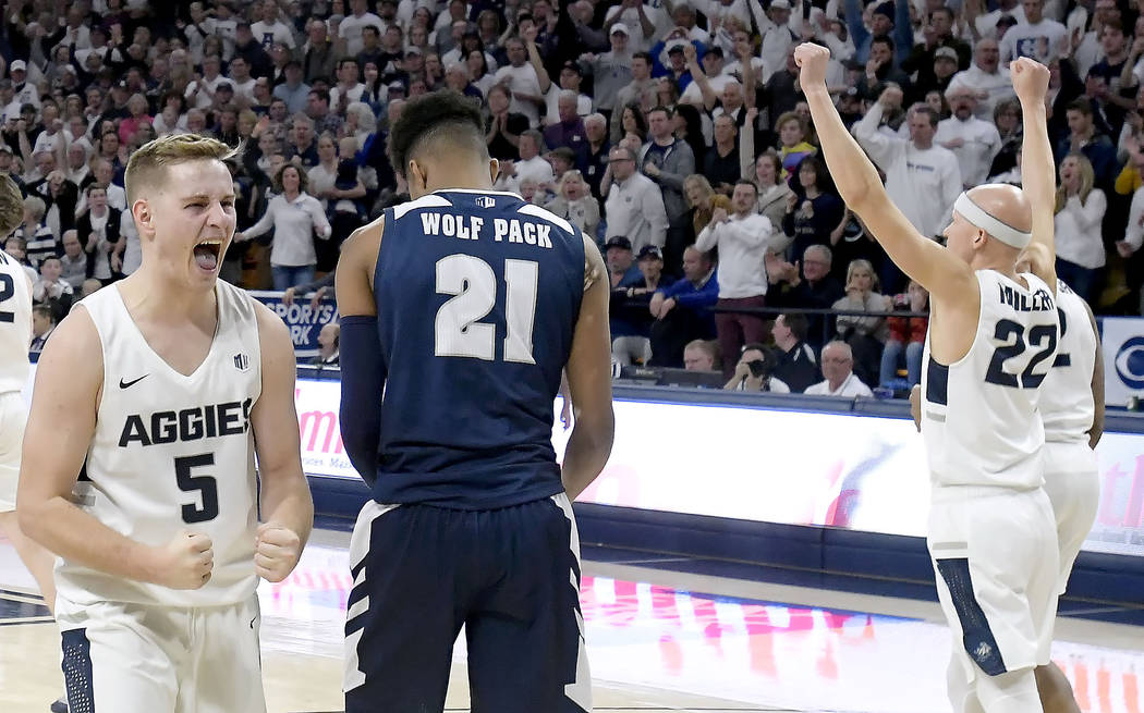 Utah State guard Sam Merrill (5) and guard Brock Miller (22) celebrate next to Nevada forward Jordan Brown (21) after Merrill drew a charge during an NCAA college basketball game Saturday, March 2 ...