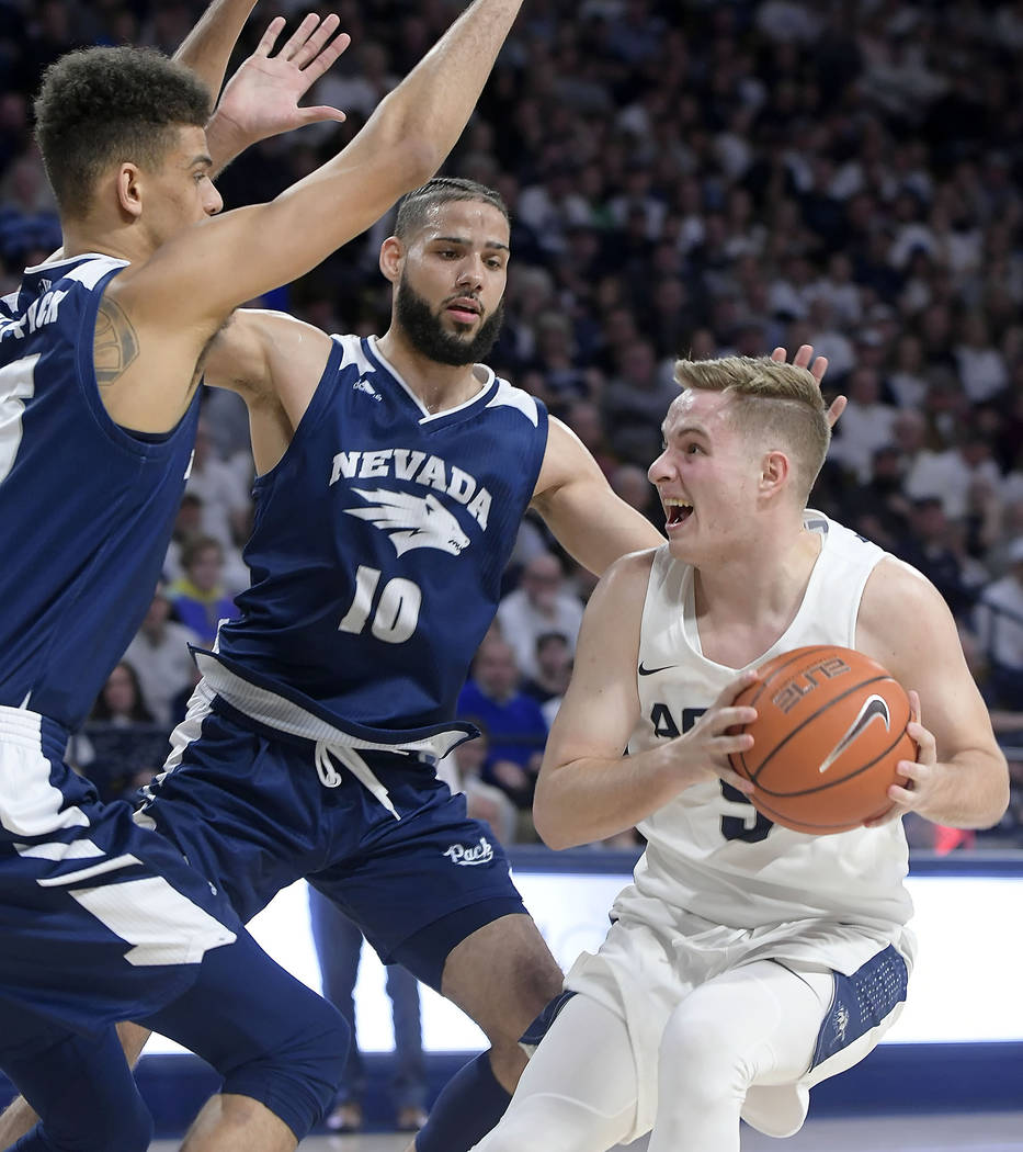 Utah State guard Sam Merrill (5) looks to shoot the ball as Nevada forward Trey Porter and forward Caleb Martin (10) defend during an NCAA college basketball game Saturday, March 2, 2019, in Logan ...