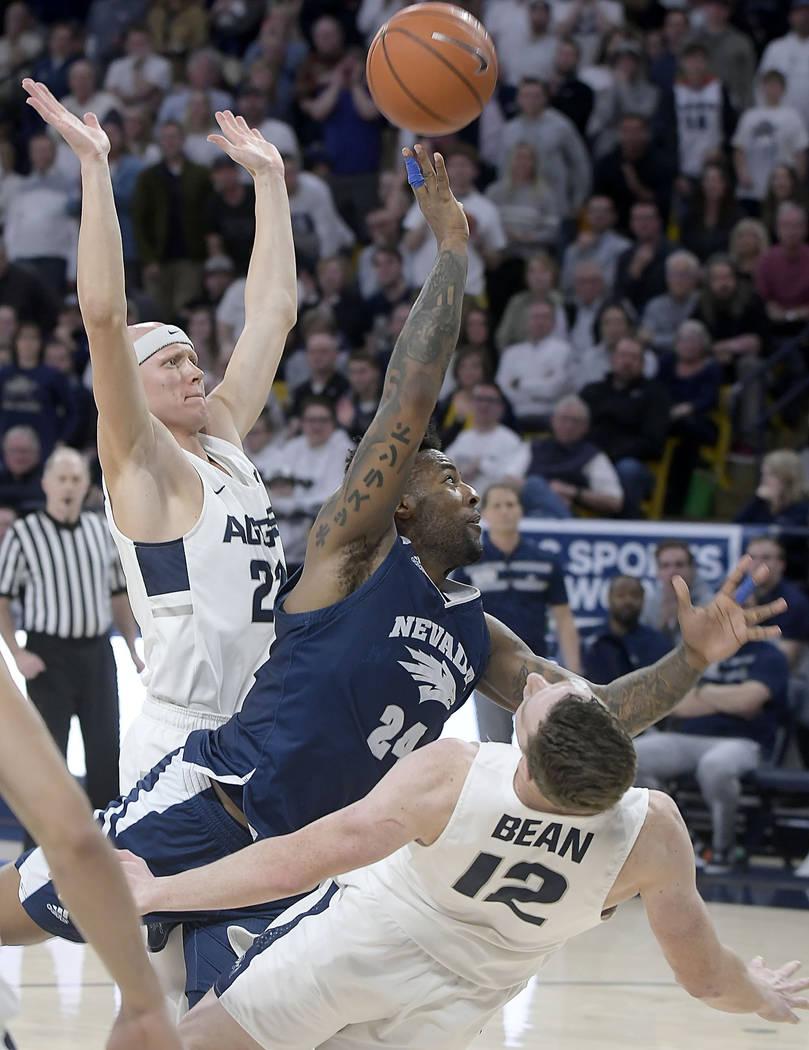 Utah State forward Justin Bean (12) draws a charge against Nevada forward Jordan Caroline (24) as Utah State guard Brock Miller helps defend during an NCAA college basketball game Saturday, March ...