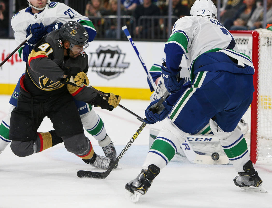 Vegas Golden Knights center Pierre-Edouard Bellemare (41) takes a shot behind his back against Vancouver Canucks goaltender Jacob Markstrom (25) during the first period of an NHL hockey game at T- ...