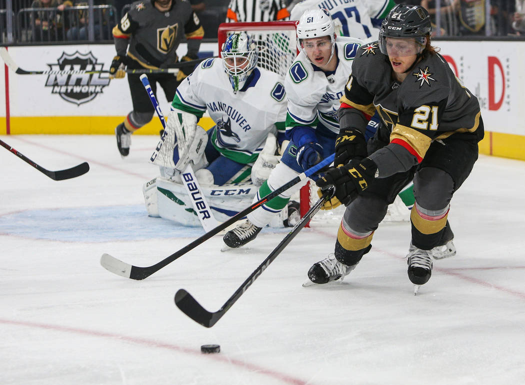 Vegas Golden Knights center Cody Eakin (21) skates with the puck as Vancouver Canucks defenseman Troy Stecher (51) trails close behind during the first period of an NHL hockey game at T-Mobile Are ...