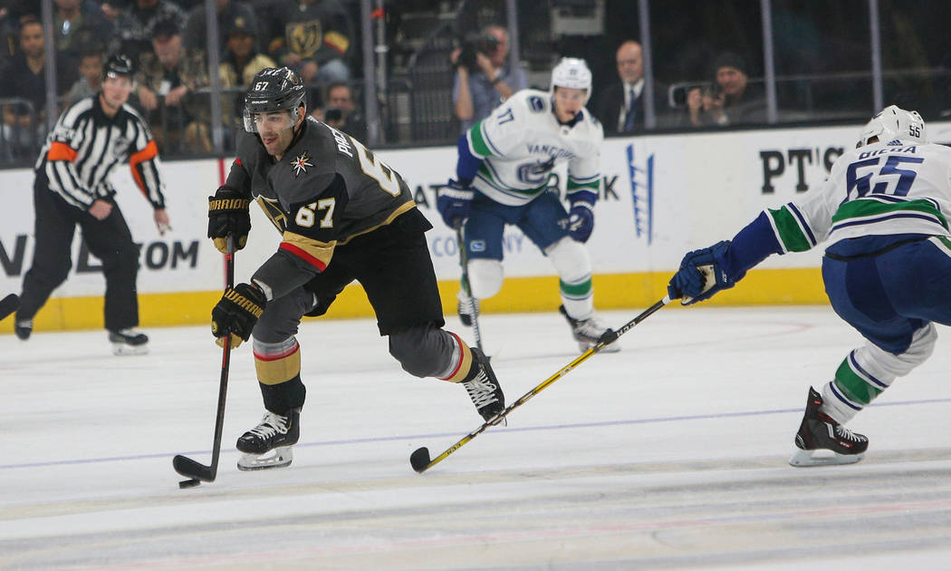 Vegas Golden Knights left wing Max Pacioretty (67) looks to pass the puck as Vancouver Canucks defenseman Alex Biega (55) reaches behind during the first period of an NHL hockey game at T-Mobile A ...