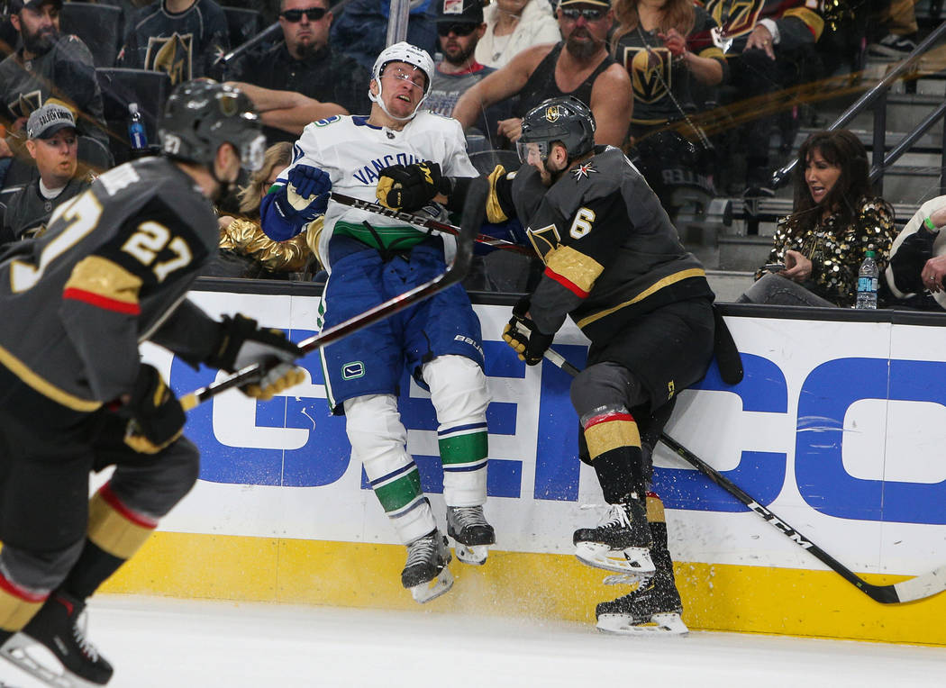 Vegas Golden Knights defenseman Colin Miller (6) pushes Vancouver Canucks left wing Antoine Roussel (26) against the wall during the second period of an NHL hockey game at T-Mobile Arena in Las Ve ...