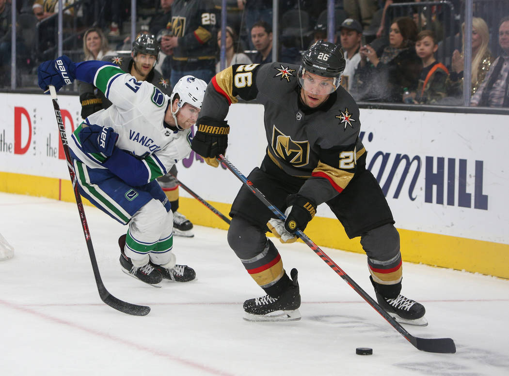 Vegas Golden Knights center Paul Stastny (26) looks to pass the puck as Vancouver Canucks defenseman Ben Hutton (27) trails behind during the third period of an NHL hockey game at T-Mobile Arena i ...