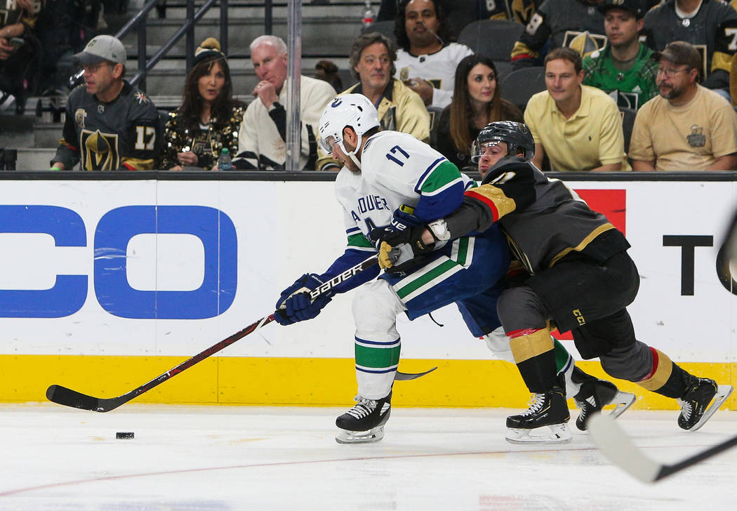 Vegas Golden Knights center Jonathan Marchessault (81) reaches behind Vancouver Canucks left wing Josh Leivo (17) for the puck during the third period of an NHL hockey game at T-Mobile Arena in La ...