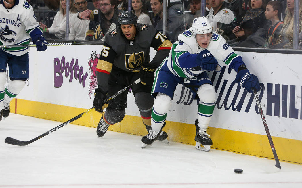 Vancouver Canucks center Adam Gaudette (88) reaches out for the puck as Vegas Golden Knights right wing Ryan Reaves (75) trails close behind during the third period of an NHL hockey game at T-Mobi ...