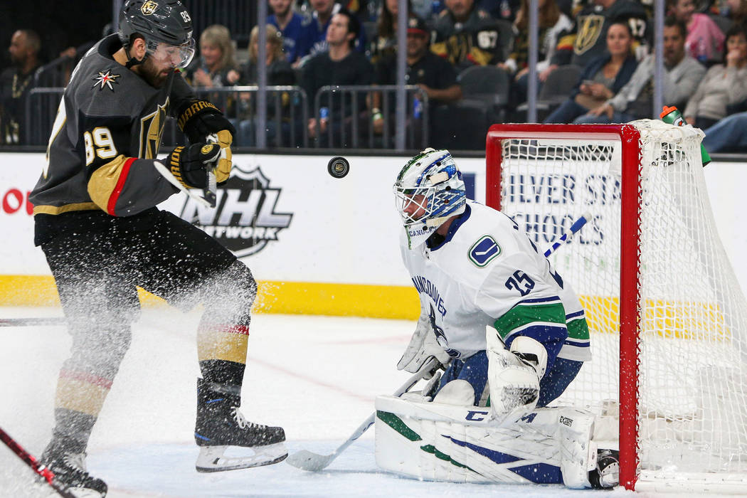 Vegas Golden Knights right wing Reilly Smith (19) takes a shot against Vancouver Canucks goaltender Jacob Markstrom (25) during the first period of an NHL hockey game at T-Mobile Arenain Las Vegas ...