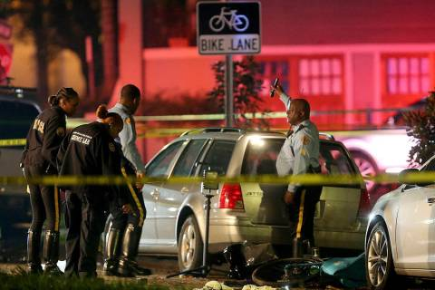 New Orleans Police examine damaged cars and bicycles on Esplanade Avenue in New Orleans after a car struck multiple people, killing several and injuring others following the Endymion Mardi Gras pa ...