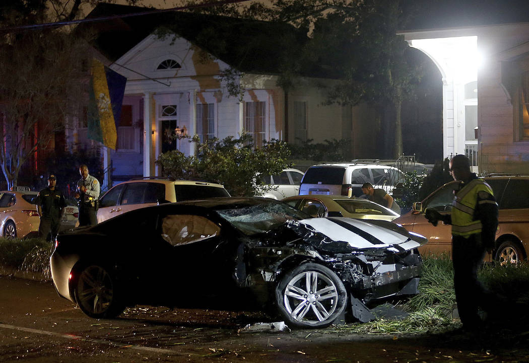 New Orleans Police examine a Chevy Camaro on Esplanade Avenue in New Orleans that struck multiple people, killing several and injuring others, after the Endymion Mardi Gras parade finished passing ...
