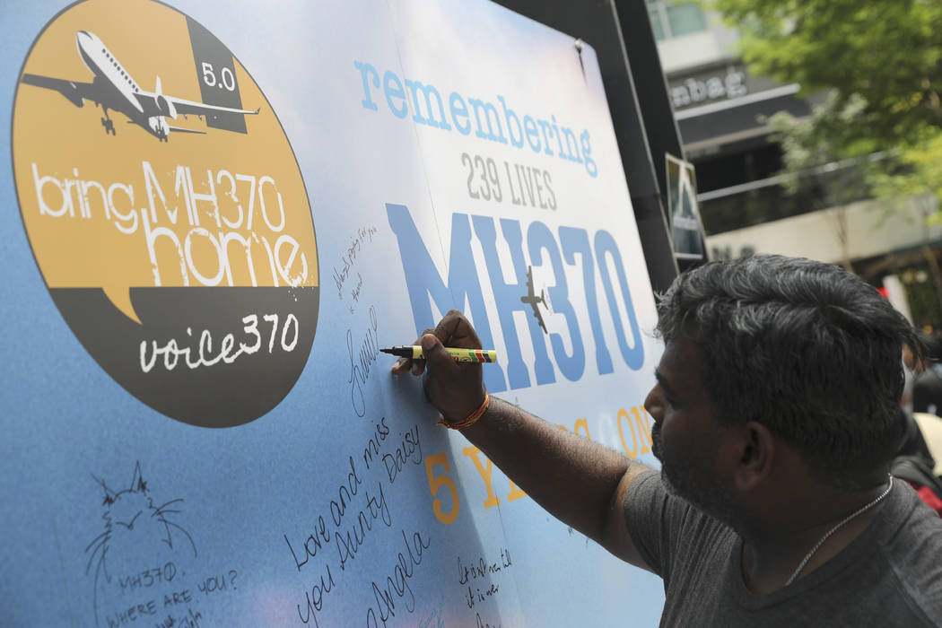 A man writes a condolence message during a Day of Remembrance for MH370 event in Kuala Lumpur, Malaysia, Sunday, March 3, 2019. Five years ago, Malaysia Airlines Flight MH370, a Boeing 777, had go ...
