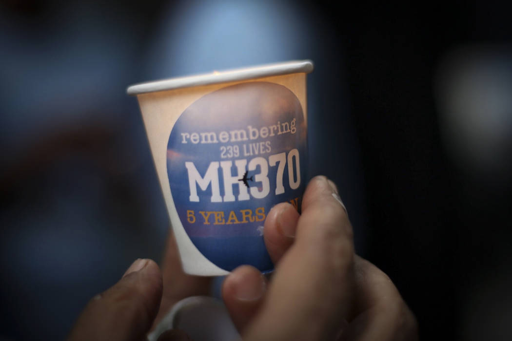 A family member of a passenger of Malaysia Airlines Flight 370, lights up a candle during the Day of Remembrance for MH370 event in Kuala Lumpur, Malaysia, Sunday, March 3, 2019. Five years ago, F ...