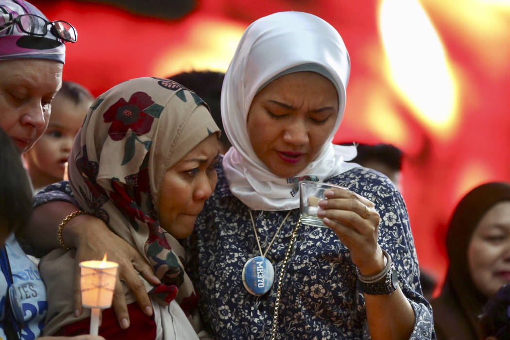 Norazlinda Ayub, left, and Intan Maizura Othaman, wife of an air crew member of Malaysia Airlines Flight 370, embrace each other during the Day of Remembrance for MH370 event in Kuala Lumpur, Mala ...