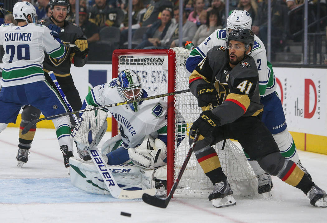 Vegas Golden Knights center Pierre-Edouard Bellemare (41) rounds the net with the puck as Vancouver Canucks defenseman Luke Schenn (2) trails close behind during the first period of an NHL hockey ...