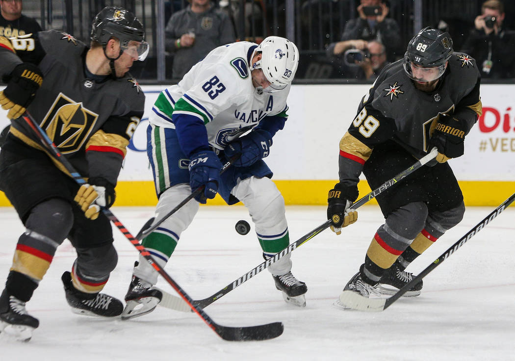 Vancouver Canucks center Jay Beagle (83) looks down at the puck as he is guarded by Vegas Golden Knights center Paul Stastny (26) and Vegas Golden Knights right wing Alex Tuch (89) during the thir ...