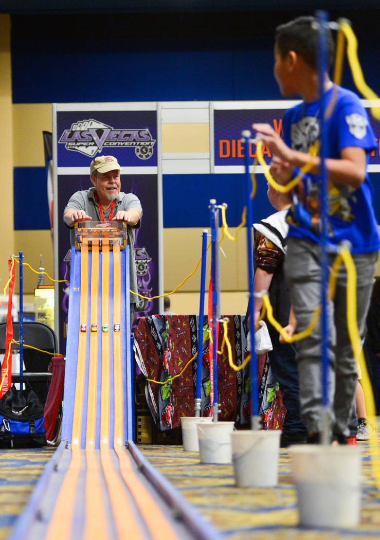 Kids run alongside the downhill Hot Wheels track as Matt Marion, left, opens the gate to start a race at Las Vegas Toy and Comic Convention at the Westgate Resort and Casino in Las Vegas, on Sunda ...