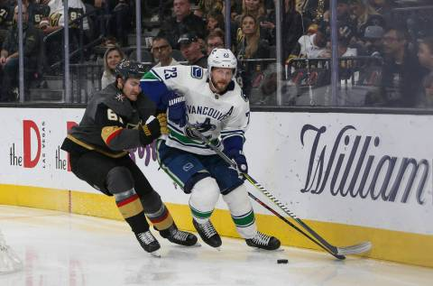 Vancouver Canucks defenseman Alexander Edler (23) looks to pass the puck as Vegas Golden Knights right wing Mark Stone (61) attempts to steal the puck during the third period of an NHL hockey game ...