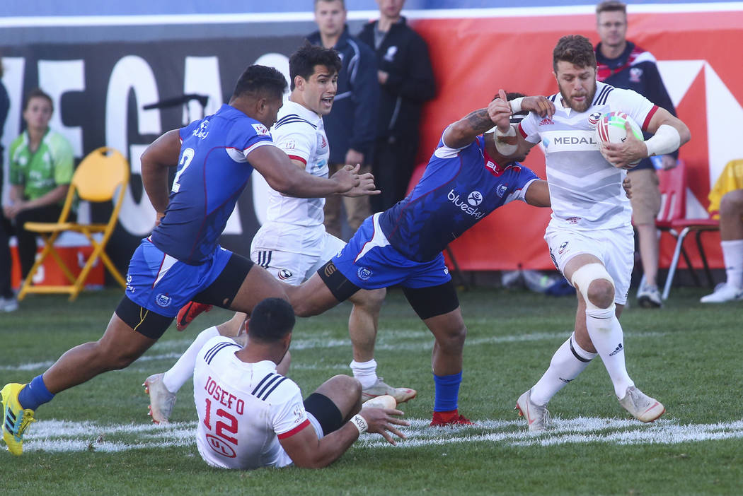 USA's Steve Tomasin, right, runs with the ball as Samoa's Melani Matavao tries to tackle him while competing in the Cup Final during the USA Sevens Rugby Tournament at Sam Boyd Stadium in Las Vega ...