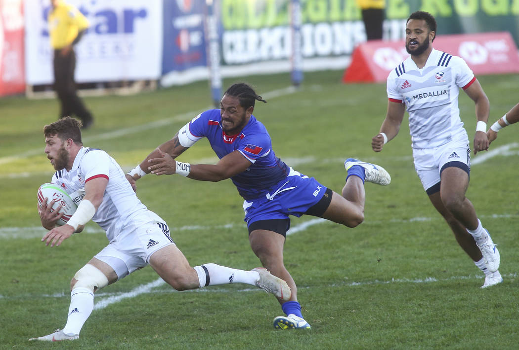 USA's Steve Tomasin, left, runs with the ball as Samoa's Siaosi Asofolau attempts to tackle while competing in the Cup Final during the USA Sevens Rugby Tournament at Sam Boyd Stadium in Las Vegas ...