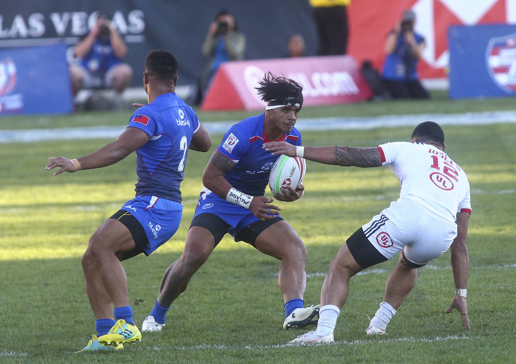 Samoa's Tofatu Solia, center, runs with the ball under pressure from USA's Martin Iosefo (12) while competing in the Cup Final during the USA Sevens Rugby Tournament at Sam Boyd Stadium in Las Veg ...