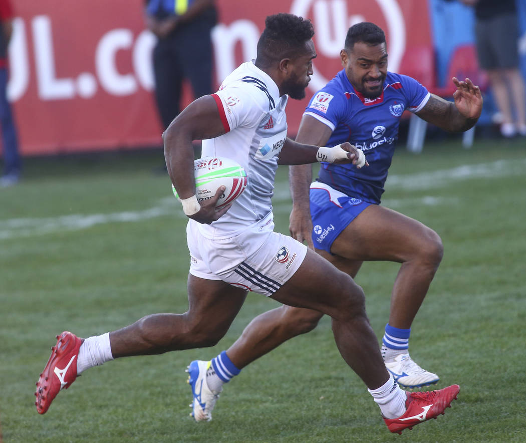 USA's Matai Leuta, left, runs with the ball against Samoa's Alamanda Motuga (2) on his way to score a try in the Cup Final during the USA Sevens Rugby Tournament at Sam Boyd Stadium in Las Vegas o ...