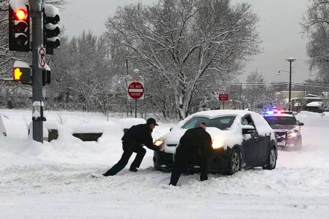 Flagstaff police officers help a motorist push a car stuck in snow in Flagstaff, Ariz., on Feb. 22, 2019. (Jennifer Brown/Flagstaff Police Department via AP)