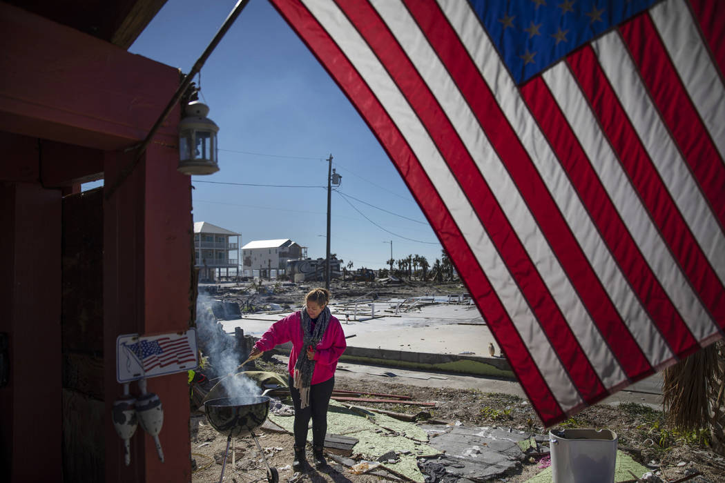 "Paulina ""Bela"" Sebastiao lights a BBQ while waiting for her damaged house from Hurricane Michael to be torn down in Mexico Beach, Fla, Friday, Jan. 25, 2019. Since the storm destroyed th ..."
