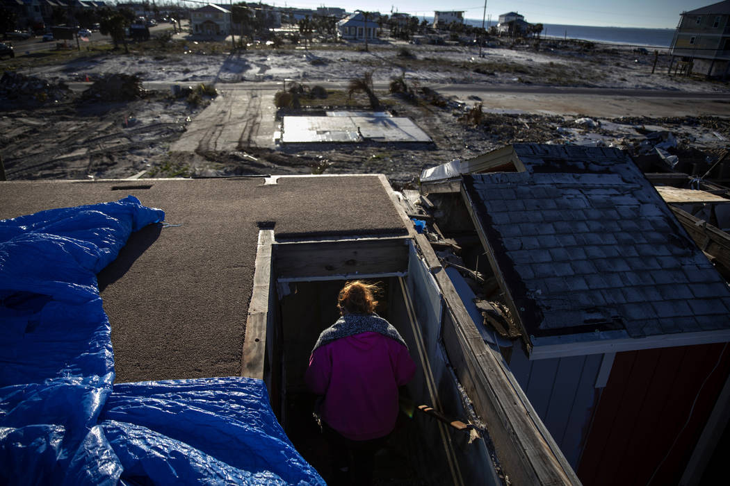 "Paulina ""Bela"" Sebastiao descends from the missing top floor of her damaged home from Hurricane Michael on the morning it is torn down in Mexico Beach, Fla, Friday, Jan. 25, 2019. The Se ..."
