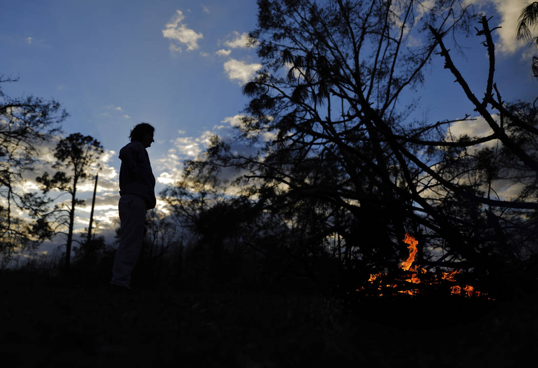 Kathryn Welch burns a pile of branches she cut off the trees that fell around her home from Hurricane Michael in Cottondale, Fla, Tuesday, Jan. 22, 2019. Welch has spent hours everyday clearing he ...
