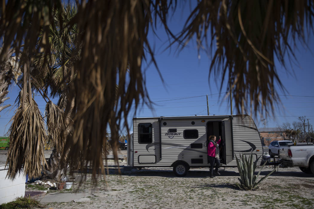 "Paulina ""Bela"" Sebastiao steps out of the trailer she's been living in after her home was damaged from Hurricane Michael on the morning it is torn down in Mexico Beach, Fla, Friday, Jan. ..."