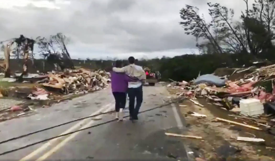 People walk amid debris in Lee County, Ala., after what appeared to be a tornado struck in the area Sunday, March 3, 2019. Severe storms destroyed mobile homes, snapped trees and left a trail of d ...