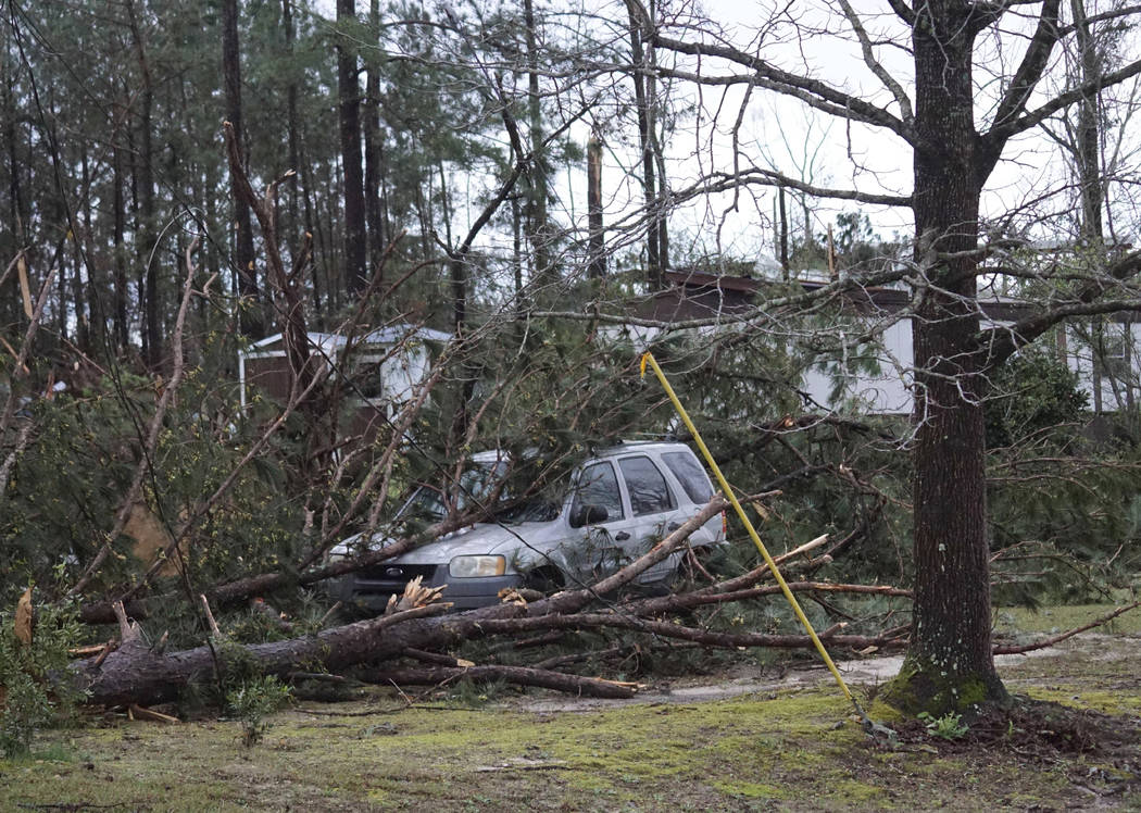 A vehicle is caught under downed trees along Lee Road 11 in Beauregard, Ala., Sunday, March 3, 2019, after a powerful storm system passed through the area. (Kara Coleman Fields/Opelika-Auburn News ...