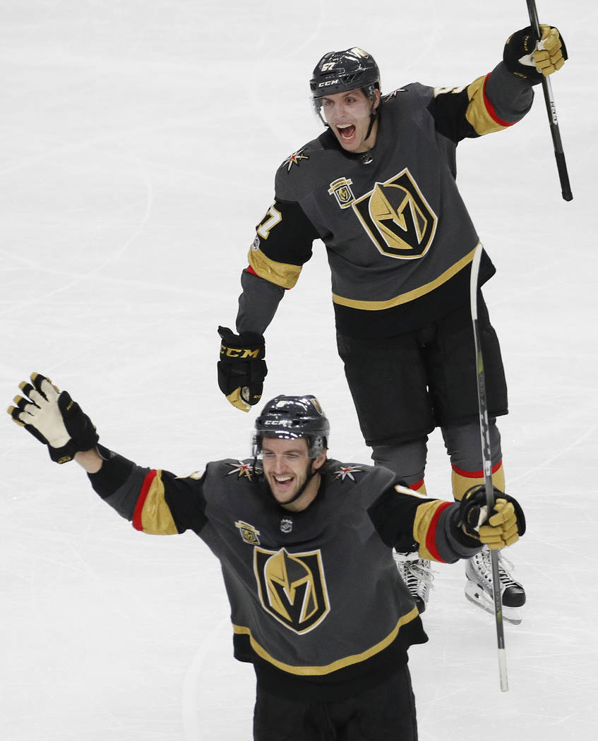 Vegas Golden Knights left wing David Perron, top, and defenseman Colin Miller celebrate after defenseman Jon Merrill scored against the Pittsburgh Penguins during the third period of an NHL hockey ...