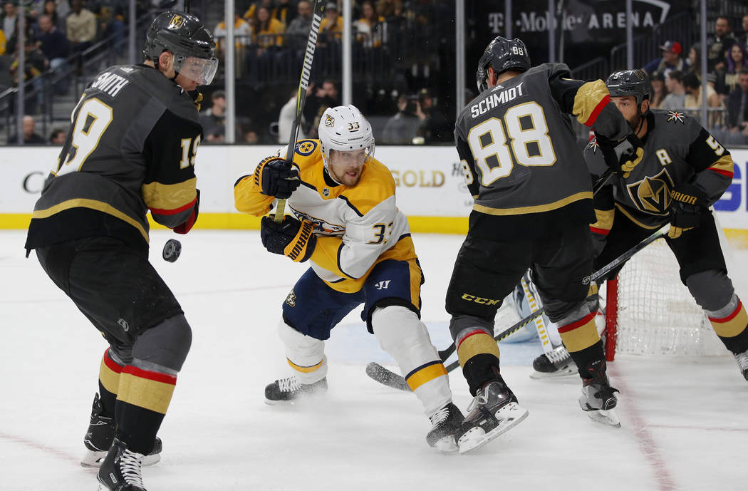 Vegas Golden Knights right wing Reilly Smith, Nashville Predators right wing Viktor Arvidsson, and Golden Knights defensemen Nate Schmidt and Deryk Engelland vie for the puck during the first peri ...