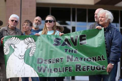 Grace Larsen, center, and Bob Furtek, right, members of Friends of Nevada Wilderness, hold up a sign during the Don't BombThe Bighorn Rally and Public Hearing at the Grant Sawyer State Office Buil ...