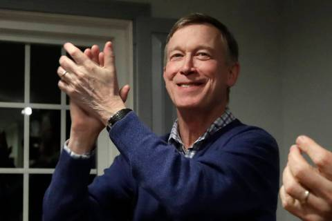 In this Feb. 13, 2019, file photo, former Colorado Gov. John Hickenlooper, left, applauds at a campaign house party, in Manchester, N.H. Hickenlooper is running for president, becoming the second ...