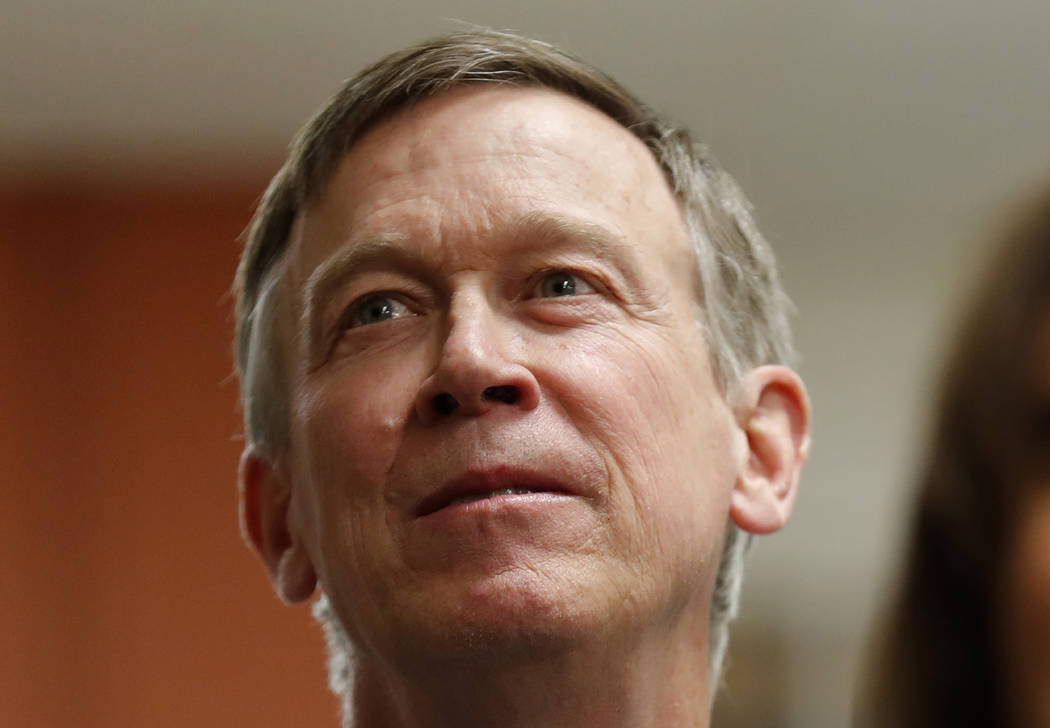 FILE - In this Feb. 23, 2019, file photo, former Colorado Gov. John Hickenlooper, left, waits to speak at the Story County Democrats' annual soup supper fundraiser in Ames, Iowa. Hickenlooper is r ...