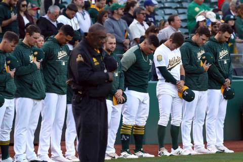 Oakland Athletics bow their heads in memory of Gretchen Piscotty, mother of right fielder Stephen Piscotty, prior to a baseball game against the Houston Astros Monday, May 7, 2018, in Oakland, Cal ...