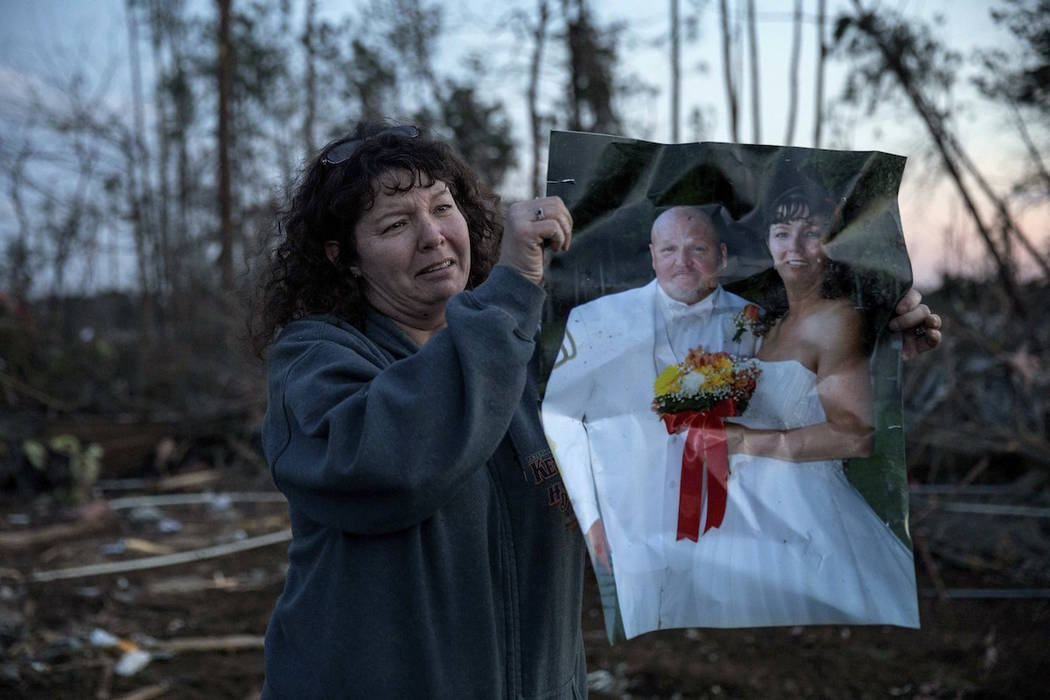 Carol Dean holds up her wedding photo to show family members after finding it in the rubble of the home she shared with husband, David Wayne Dean, who died when a tornado destroyed the house in Be ...