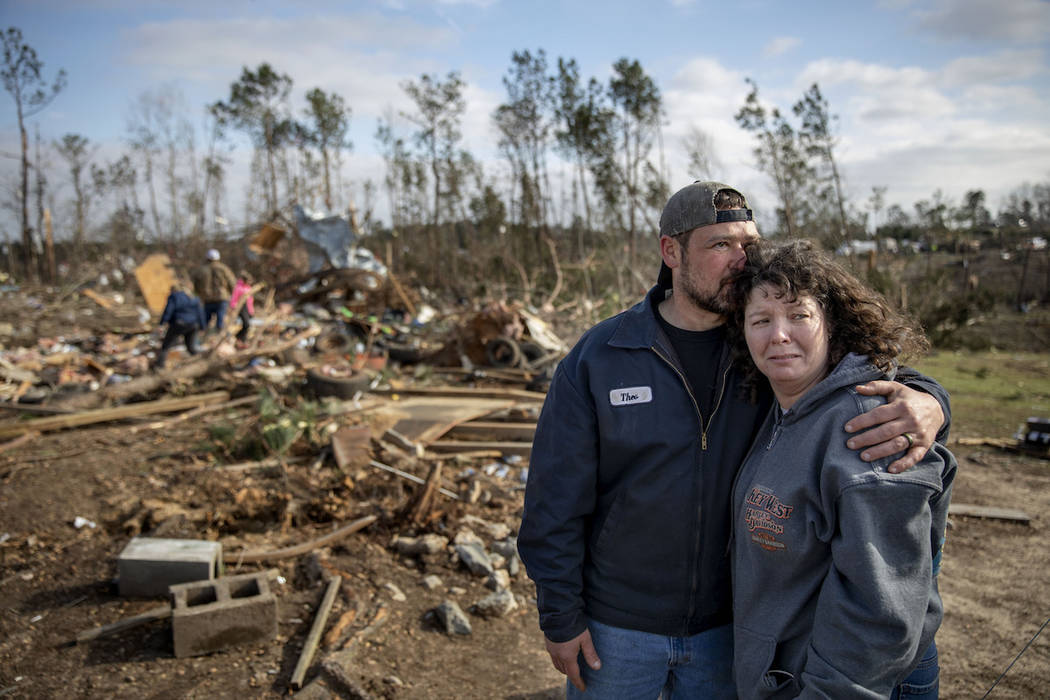 Carol Dean, right, is embraced by David Theo Dean as they sift through the debris of the home Carol shared her husband and David's father, David Wayne Dean, who died when a tornado destroyed the h ...