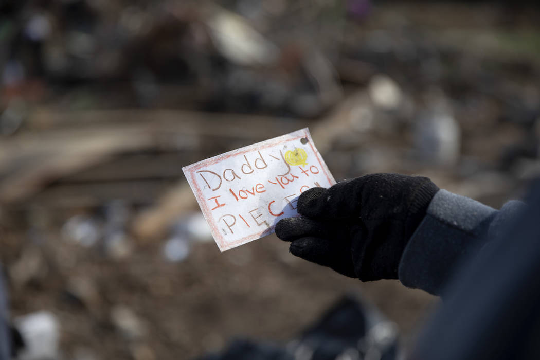 Carol Dean holds a note her husband, David Wayne Dean, received from his daughter on Father's Day as she sifts through the rubble of the home the couple shared the day after her David died when a ...